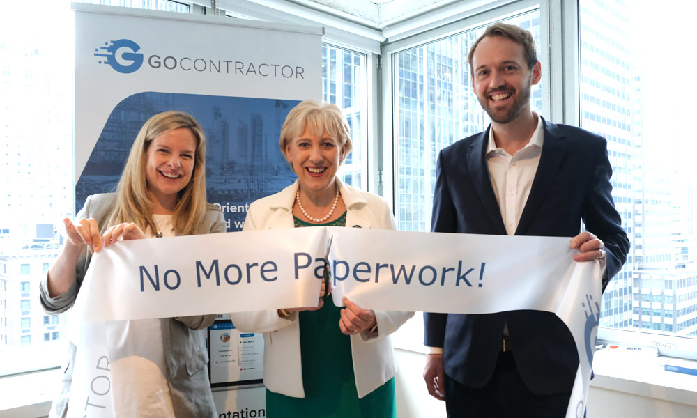 "Julie Currid, Minister Humphreys and John Naughton holding a ribbon which reads ""No More Paperwork"""