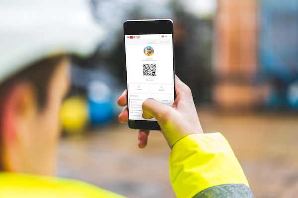Safety manager spot checking construction subcontractor with QR code